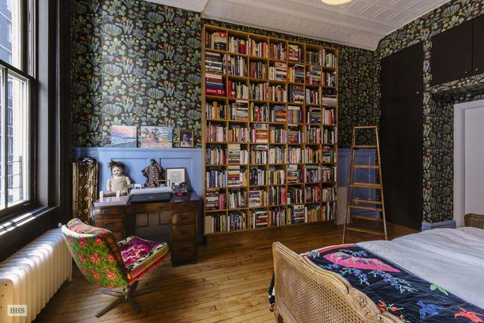 Våga mönster! Tapet av Josef Frank för Svenskt tenn, böcker i mängder, säng med rotting och en omklädd fåtölj i 50-tals modell. Bild via Brown Harris Stevens.