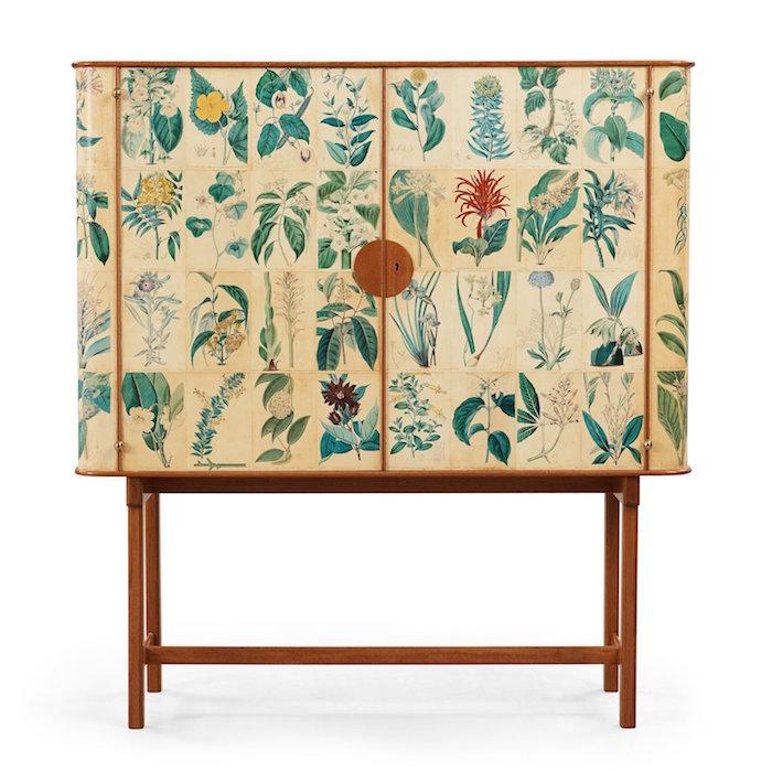 """JOSEF FRANK, SKÅP, TAPETSERAT MED SYDENHAM EDWARDS HANDKOLORERADE BOTANISKA GRAVYRER, FIRMA SVENSKT TENN, SANNOLIKT 1950-TAL. Mahogny, skåpets dörrar och sidor tapetserade med engelska botaniska, handkolorerade gravyrer ur Sydenham Edwards """"The Botanical Register"""", James Ridgway & Sons, London, 1800-tal, inredning med tre lösa hyllor. Mått 120 x 41 cm, höjd 130 cm. Modellen är känd sedan Josef Franks första år i Sverige. Redan i Wien ritade Frank emellertid liknande skåp för sin firma Haus & Garten, på Hofmobiliendepot finns ett snarlikt skåp som är klätt med textil. Jämför även Bukowskis Moderna auktion 569, hösten 2012, nr 485. Josef Franks klädda skåp har haft olika typer av yta, ibland tyg, målat tyg eller matelasserat tyg, skinnklädsel eller det som kom att bli vanligast, planscher ur framför allt """"Lindmans Flora"""". Carl Lindman utgav Bilder ur"""
