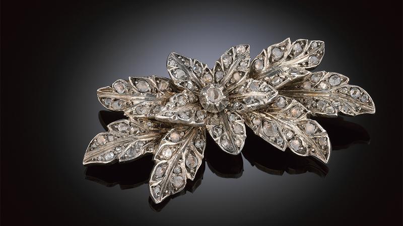 Brosch 18 kt guld och silver i form av ett blomstermotiv med små rosenstenar.