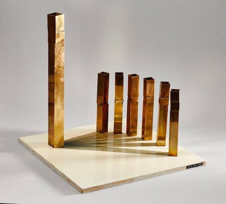 """Skulptur Lasse Stevenfeldt (1930-2014), bemålad, """"Ett på sex"""", mässing på bemålad träplatta, ej signerad, 30x30 cm, höjd: 30 cm. Utropspris 2 000 SEK."""