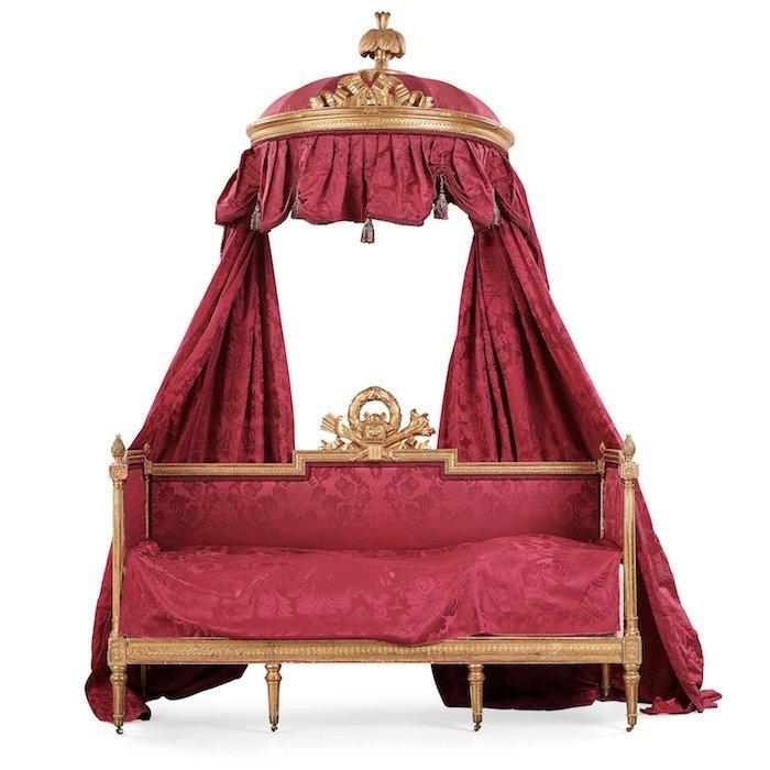""". HIMMELSSÄNG, LIT À L'ANGLAISE, TILLSKRIVEN ERIK ÖHRMARK (MÄSTARE I STOCKHOLM 1777-1813), GUSTAVIANSK. Förgylld och bronserad. Skulpterad dekor. Sänghimmel med krönande plym och bandrosett. Säng med pilkoger, fackla och lagerkrans. Ramverk med flätband och pärlstav. På fottrissor av mässing. Röda sammetstyget inköpt i Frankrike vid 1940-talets slut av Karl Gustav Lagerfelt. Sängens längd 195, bredd 89, höjd 131 cm. Smärre slitage. FÖLJERÄTT Nej PROVENIENS Säbylund, Närke. Upptagen i Claes de Frietzckys egenhändiga förteckning från den 11 juli 1789 på Säbylund """"Förteckning på Meublerne vid Säbylund och hvad de kosta i inkiöp med frackt"""", Kungliga biblioteket: """"Sängkammaren... 1 Gustaviad Säng af samma slags Damast* och förgylda lister garnerad med röda och hvita suiljoner och tofsar"""". *För varje rum inleder Claes de Frietzcky med att beskriva väggbeklädnaden, i sängkammaren """"af Ost Indiskt röd Damast med förgylda lister och 2ne förgyllda dörrstycken"""". UTROPSPRIS 50 000 - 75 000 SEK/5 175 - 7 763 EUR"""