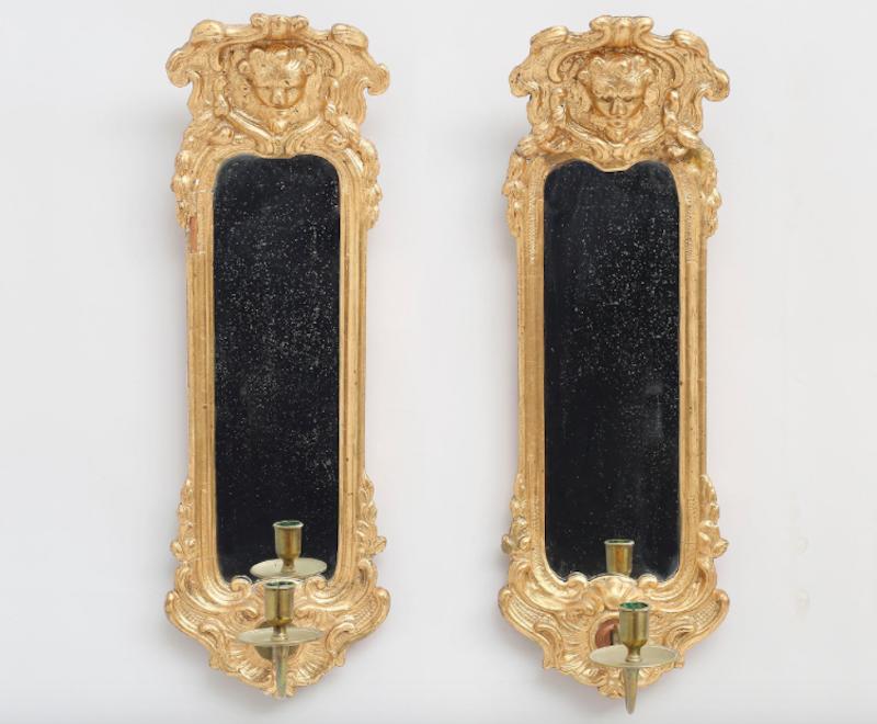 Ett par spegellampetter i Stockholmsarbete i skuren dekor samt pastellagedekor med utsvängt krön med dekor av bland annat lejonhuvuden och girlander, förgyllda med slagmetall och ljusarmar i mässing. Utrop är