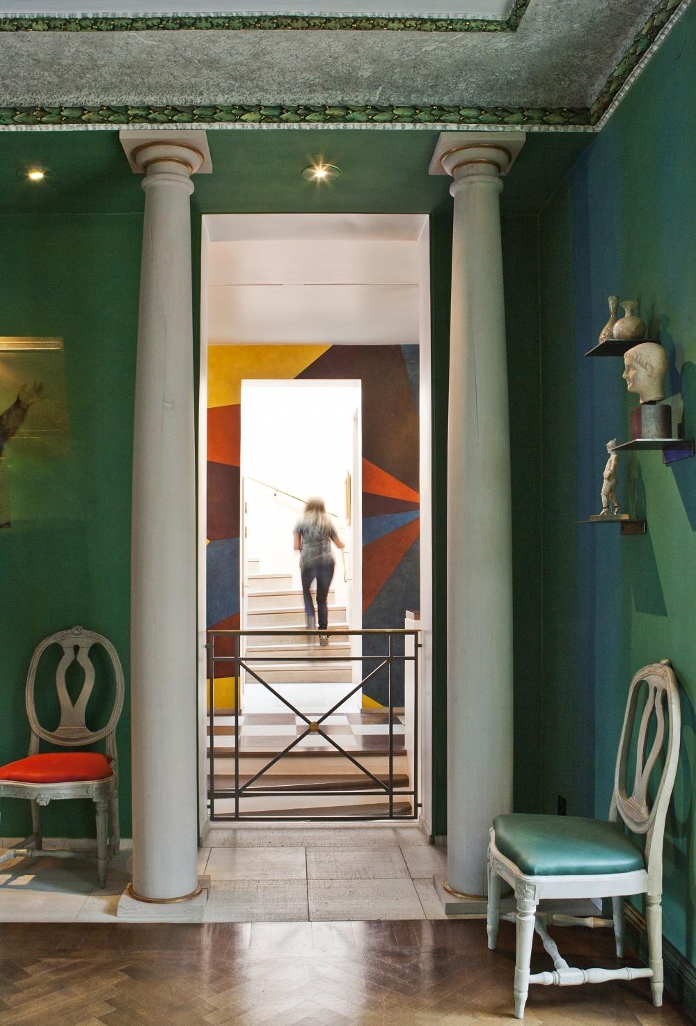 Durch die von ionischen Säulen aus Massivholz flankierte Wandöffnung strahlt die bunte Wandfarbe der Halle bis ins Esszimmer