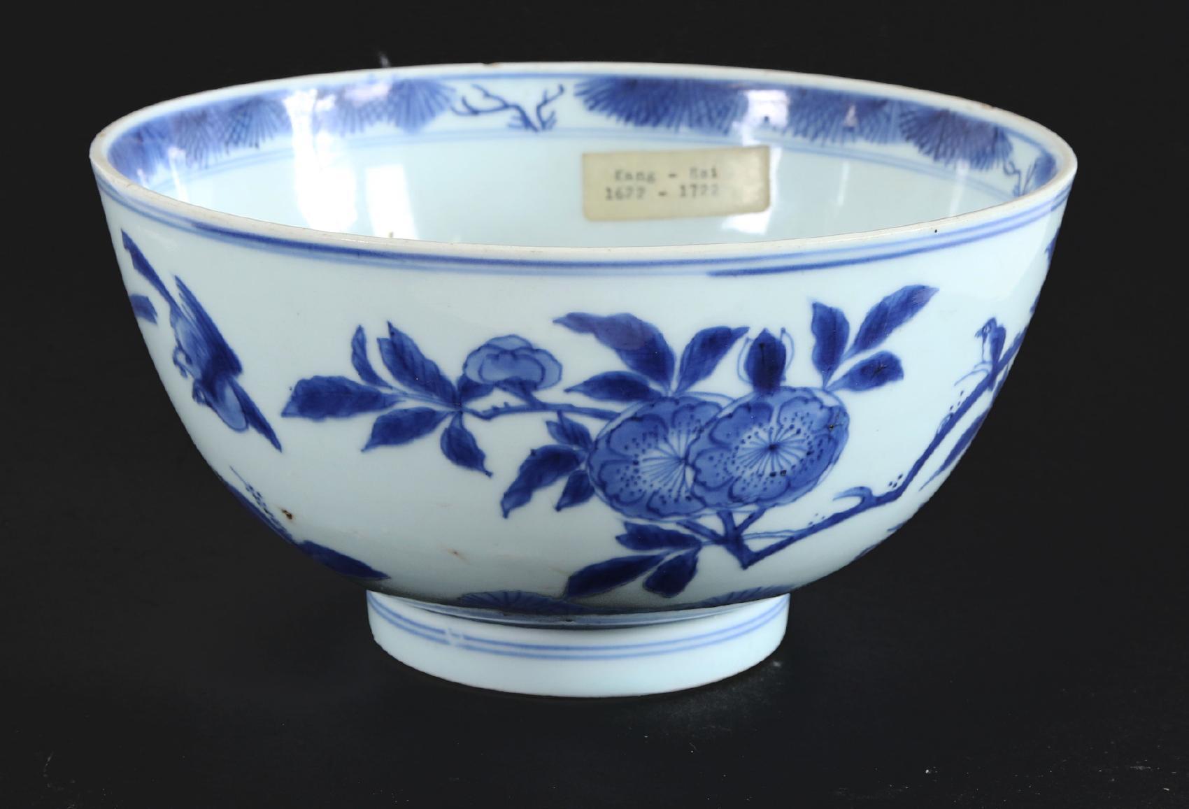 Skål, Kina, Kangxi, omkring år 1700 Underglasyrblå med dekor av fåglar och träd. Undertill med Ming-sigill. Glasyrmistor, tre kantnaggar. (Höjd 11, diameter 21). Startpris: 100 SEK.