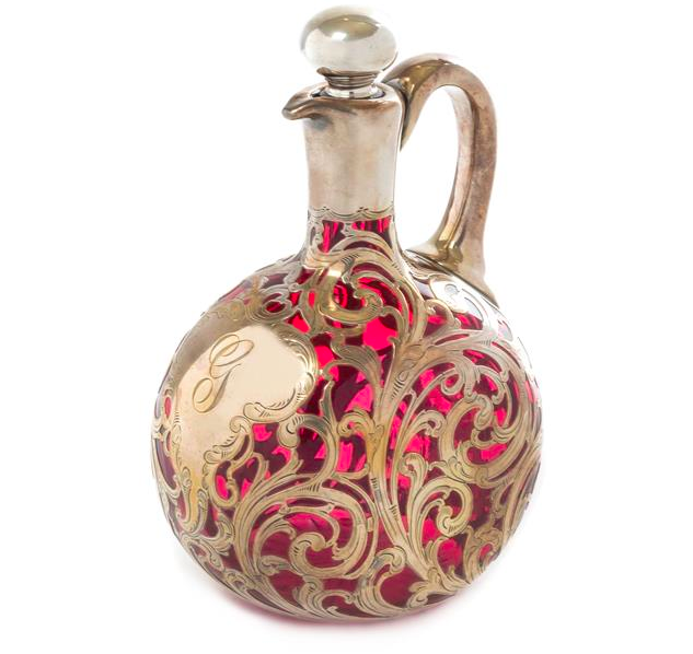 An Art Nouveau Silver Overlay Glass Cruet, of flattened bottle form with an applied handle and stopper, with allover scrolling foliate overlays and a star cut base, silver by Alvin Mfg. Co., Providence, RI, numbered R141. Low estimate: 400 USD. Leslie Hindman Auctioneers