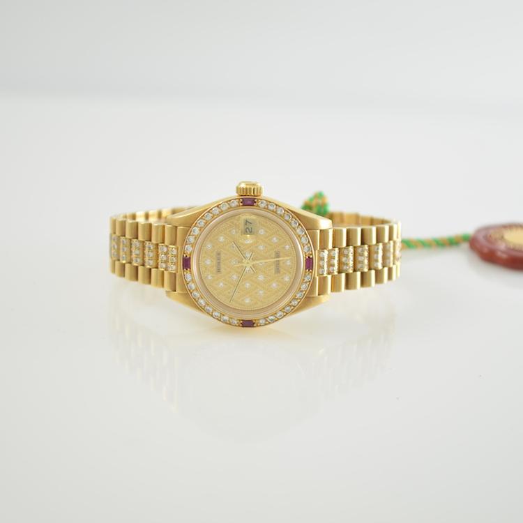 ROLEX Damenarmbanduhr Passend zum vorigen Modell präsentiert sich nun der Oyster Perpetual Dayjust als exklusiver Chronometer für die Dame. Ebenfalls aus Gelbgold gefertigt, ist der Besatz aus Brillanten aufwändiger gestaltet und wird harmonisch durch vier Rubincarrés ergänzt. Schätzpreis: 5.500-9.000 EUR. Henry's Auktionshaus