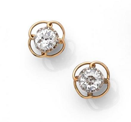 Paire de boutons d'oreilles en or gris et or jaune 18k (750) ornés chacun d'un diamant taille ancienne entouré d'un filin formant quatre boucles.  Estimation basse: 5 500 €